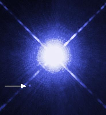 Pilen pekar på den vita dvärgen Sirius B, och den stora stjärnan är Sirius A.